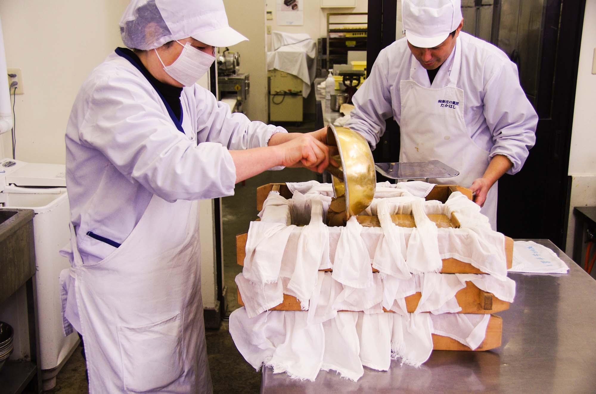 山形県アンテナショップおいしい山形 つくり手を訪ねて 有限会社新庄の菓匠たかはし:                 餅米とうるち米に黒砂糖や味噌、醤油などを加えた生地を木製の型に流し込んでいきます。